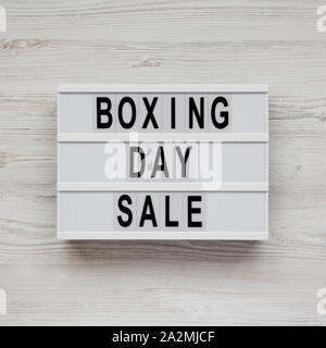 'Boxing day sale' words on a lightbox on a white wooden surface, top view. Overhead, from above, flat lay. - Stock Photo