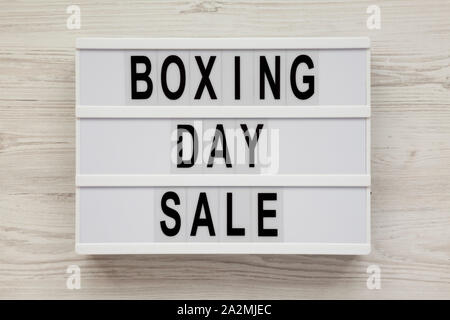 'Boxing day sale' words on a modern board on a white wooden surface, top view. Overhead, from above, flat lay. - Stock Photo