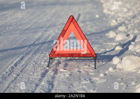 Autoilija pulassa talvella ja asettamassa varoituskolmiota sekä soittamassa apua. - Stock Photo