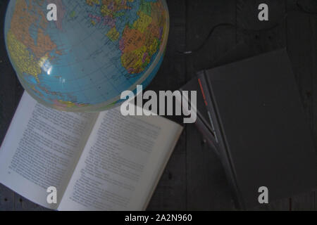 Earth ball with books on gray background - Stock Photo