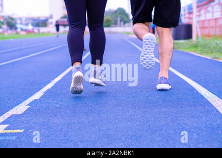 Closeup shoe. A couple jogging and walking together on the running track. Sport and exercise concept. - Stock Photo