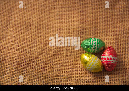 A decorative background for Easter with brightly colored eggs on a brown sackcloth and space to add texts or graphics. Copy Space