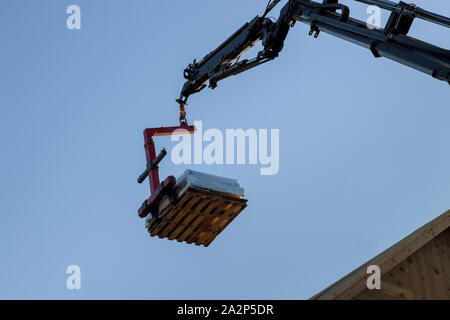 Construction building industry details in progress boom truck forklift crane roof into plate on new home - Stock Photo