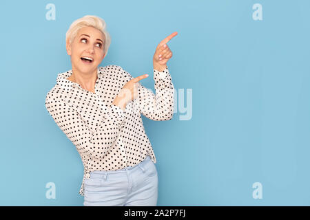 Attractive happy adult woman pointing on empty copy space. Emotions. Blue studio background. - Stock Photo