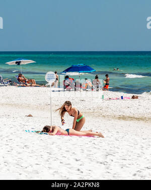 two teenage girls with people in the background on the beach at Seaside, FL - Stock Photo