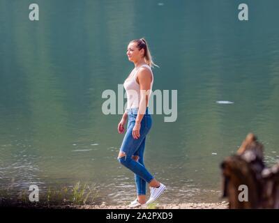Young woman wearing Blue denim pants denims is walking along lake coastline - Stock Photo
