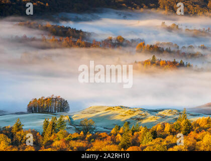 The village of Elterwater is hidden under a blanket of fog during a beautiful temperature inversion on a frosty autumn morning in the Lake District. - Stock Photo