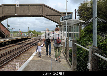 Family with child & rucksacks walking along railway platform at Southease Station after getting off a train from Brighton East Sussex UK KATHY DEWITT - Stock Photo