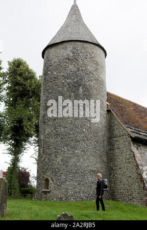 A woman walker with rucksack stands next to the Church of St Peter round tower in the Southease village of East Sussex, England UK  KATHY DEWITT - Stock Photo