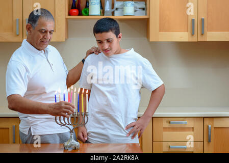Happy family is lighting a candle celebrating together Jewish holiday Hanukkah. Jewish Dad and teenager son or grandfather with grandson lighting Chanukkah Candles in a menorah for the holdiay - Stock Photo