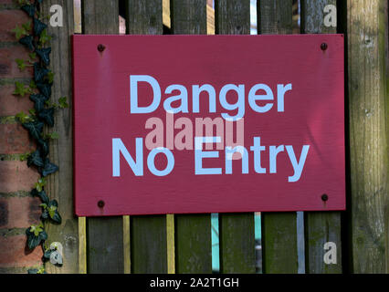 Danger No Entry signboard on an old perimeter wall gate - Stock Photo