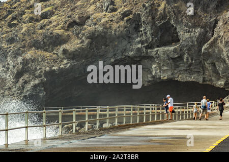 A view of huge cave along the promenade from central square of Candelaria. powerful sea waves crashing on a concrete shore. Tenerife, Spain. - Stock Photo