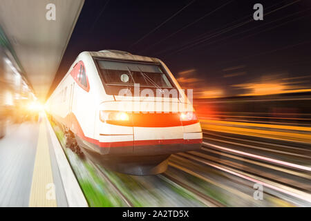 Train rides on a trip at the railway station in the city at night. - Stock Photo