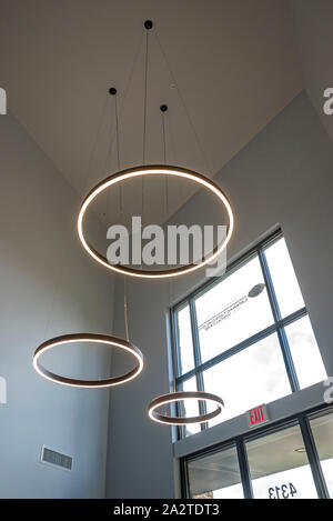 Large circular lights hanging from the ceiling inside a doctor's office entrance. - Stock Photo