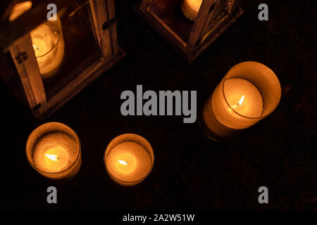 Many burning candles in glass and wooden lanterns on dark ground outdoor at night. Romantic party area. Diwali fire holiday - Stock Photo