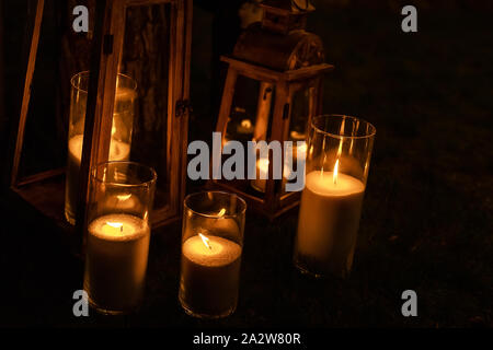 Many burning candles in glass and wooden lanterns on dark ground outdoor at night. Romantic party area. Diwali fire holiday