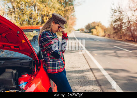 Broken car. Sad woman standing on road by her auto with hood open waiting for help - Stock Photo