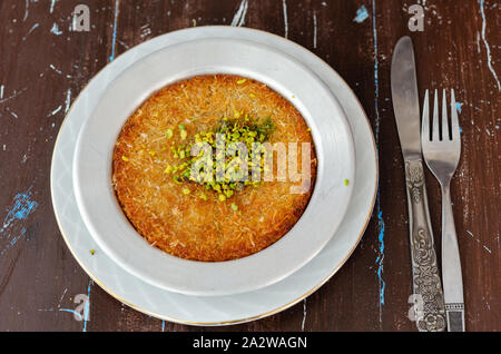 Delicious traditional Turkish dessert:  Kunefe  kadayif with pistachio and cheese - Stock Photo