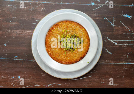 Delicious traditional Turkish dessert:  Kunefe  kadayif with pistachio and cheese - Stock Photo