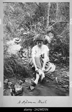 Photograph - by A.J. Campbell, Victoria, circa 1890, A woman is seated by a stream putting on a stocking. Her other foot is bare and a hat and other items of clothing lie on the ground behind her - Stock Photo