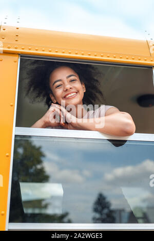 African girl going to school by bus looking out the window smiling cheerful close-up - Stock Photo