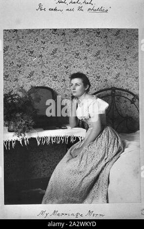 Photograph - by A.J. Campbell, Victoria, circa 1890, A young woman sits on the edge of a bed. She rests her elbow on a side table and has her hand against her cheek. There is a looking glass and a vase of flowers on the table. The wall paper is highly decorative - Stock Photo