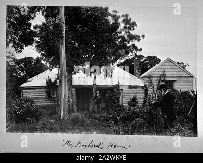 Photograph - by A.J. Campbell, Victoria, circa 1890, A man, holding a rifle, standing in front of a wooden building which has a corrugated iron roof. There is a second building on the right and there is a large tree in the foreground. A bearded man wearing a bowler hat stands on the right - Stock Photo