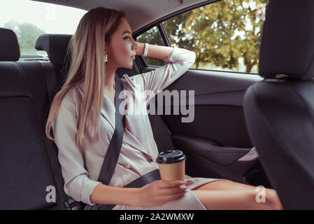 beautiful business woman rides in taxi inside car, holds cup coffee tea, has snack breakfast, goes work important meeting, has rest looks out window - Stock Photo