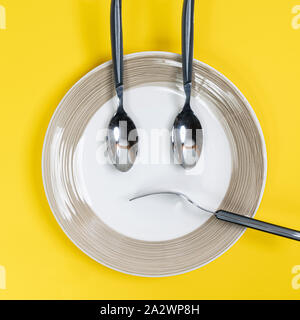 the crockery placed on the plate to form a sade face - Stock Photo