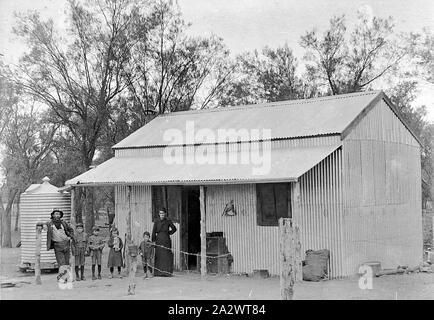 Negative - Merbein District, Victoria, circa 1910, Bill Smith and his family outside Bob Telford's hut. The hut is constructed entirely of corrugated iron, with timber verandah supports. It is a rural setting with a water tank at the side - Stock Photo