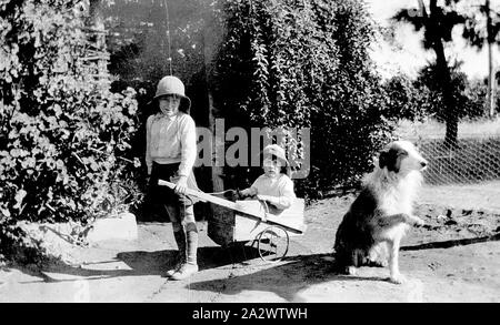 Negative - Merbein District, Victoria, circa 1935, Two children in a back yard. One is seated in a billy cart drawn by the other. A dog sits on the right with its paw raised - Stock Photo