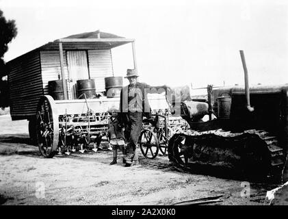 Negative - Corrigin, Western Australia, 1932, An itinerant worker with his small daughter. Their mobile home is in the background and there is a caterpillar tractor and a combine in the front - Stock Photo