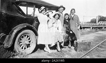 Negative - Swan Hill, Victoria, circa 1930, A man and four women beside a car. A bridge over the Murray River is in the background. There is a suitcase on the ground in front of the group while a railway line is visible at the bottom right hand corner - Stock Photo