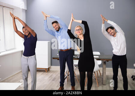 Portrait Of A Smiling Young Businesspeople Doing Yoga At Office - Stock Photo