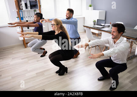 Smiling Multi Ethnic Young Businesspeople Doing Sit-ups Together At Workplace - Stock Photo