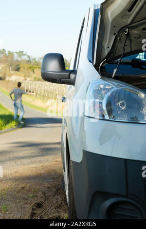 person hitching a life after their van has broken down - Stock Photo