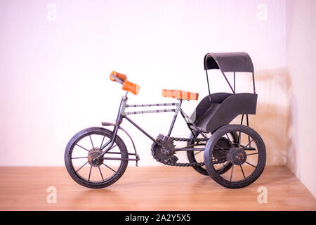 Toy bicycle or Indian style rickshaw isolated on a pink background - Stock Photo