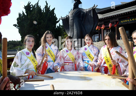 Qingdao, China's Shandong Province. 3rd Oct, 2019. Contestants for the Miss Tourism World 2019 Global Finals learn to play drums at a scenic spot in Qingdao, east China's Shandong Province, Oct. 3, 2019. Some contestants visited Langyatai scenic spot and experienced the traditional culture in Qingdao. Credit: Li Ziheng/Xinhua/Alamy Live News - Stock Photo