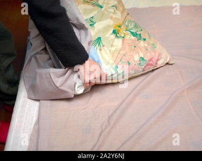 Close-up of female hands arranging a bed, indoor shot - Stock Photo