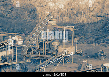 Machinery at a quarry with piles of sand and aggregate in the background.  With colour toning - Stock Photo