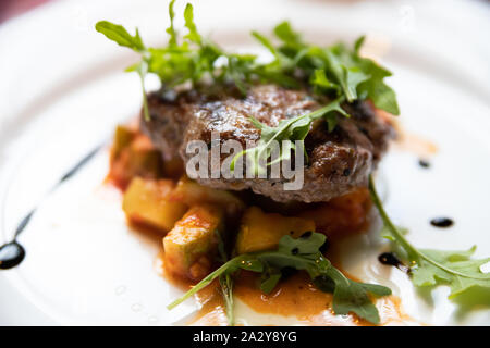 Meat cutlet with orange pieces of stewed pumpkin decorated with sauce and green arugula leaves - Stock Photo