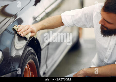 Man in a white shirt. Worker wipes a car. Male holding a rag in his hand - Stock Photo