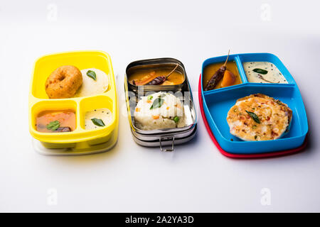 Assorted South Indian tiffin / lunch box food in group, includes idli vada, uttapam/uthappam, upma with sambar and chutney - Stock Photo