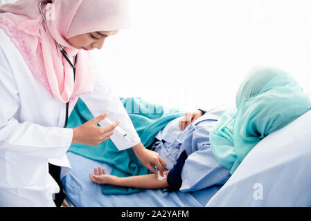 A beautiful young Muslim woman doctor wearing headphones, hand-held syringes, and a cotton ball is about to be injected into the arm of a sick patient - Stock Photo