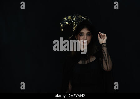 An Asian beautiful woman model dressed as a witch and a witch's hat costume smile and acting on Halloween party with dark background. copy space - Stock Photo