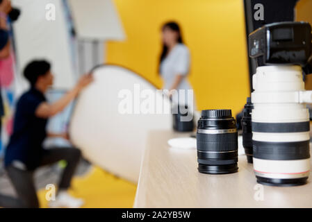 Behind the scenes, photographers are using reflex to shooting pictures of beautiful young women models smiling and posing in the studio with the backd - Stock Photo