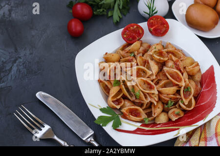 Conchiglie Italian pasta shells with cherry tomatoes and tomato sauce on dark background, horizontal orientation, top view, copy space - Stock Photo