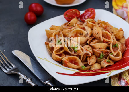 Conchiglie Italian pasta shells with cherry tomatoes and tomato sauce on dark background, horizontal orientation, closeup - Stock Photo