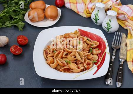 Conchiglie Italian pasta shells with cherry tomatoes and tomato sauce on dark background, horizontal orientation, closeup - Stock Photo