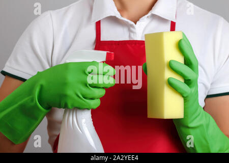 Close-up of a woman in an apron and protective gloves holds a spray bottle and a sponge in hands. - Stock Photo